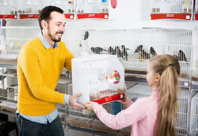 Клетка мужского продавца предлагая с канереечной птицей стоковые изображения rf