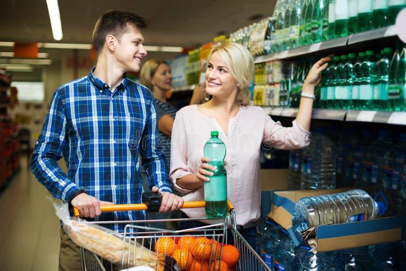 Клиенты выбирая бутылку воды стоковое фото
