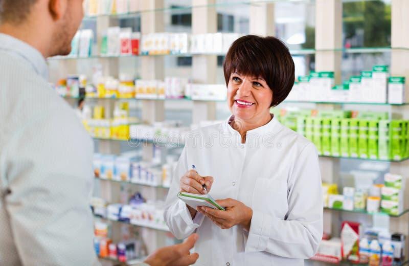 Клиенты порции аптекаря женщины в аптеке стоковое фото