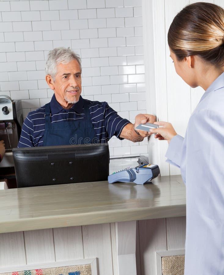Клиент давая кредитную карточку к кассиру на магазине стоковые изображения rf