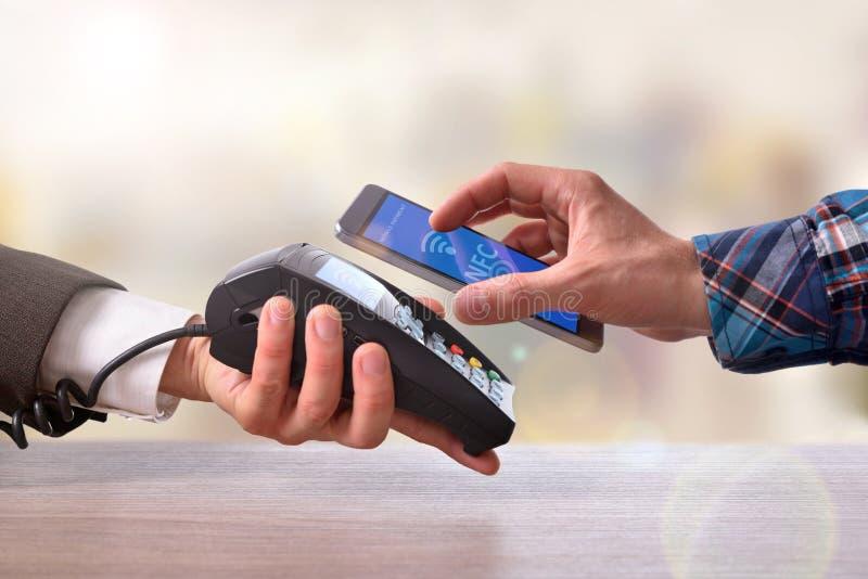 Клиент оплачивая купца с технологией nfc мобильного телефона стоковое изображение