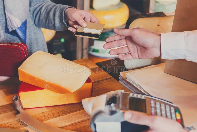 Клиент оплачивая для заказа сыра в бакалейной лавке стоковые изображения