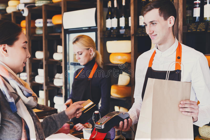 Клиент оплачивая для заказа сыра в бакалейной лавке стоковые фото