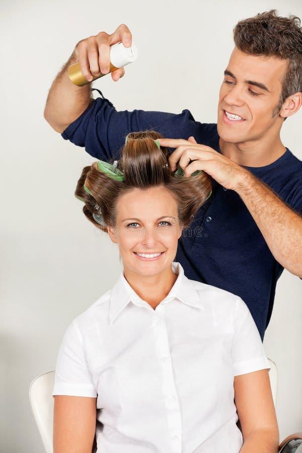 Клиент с установкой парикмахера завивает с стоковые фото