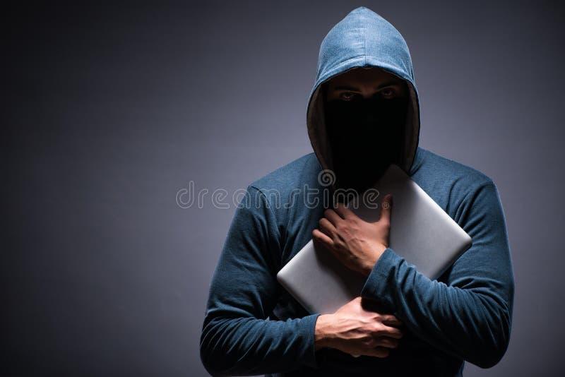 Клобук хакера нося в темной комнате стоковая фотография rf
