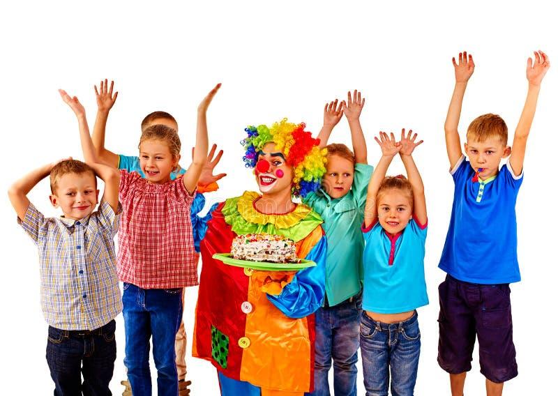 Клоун держит торт на дне рождения с детьми группы стоковая фотография rf