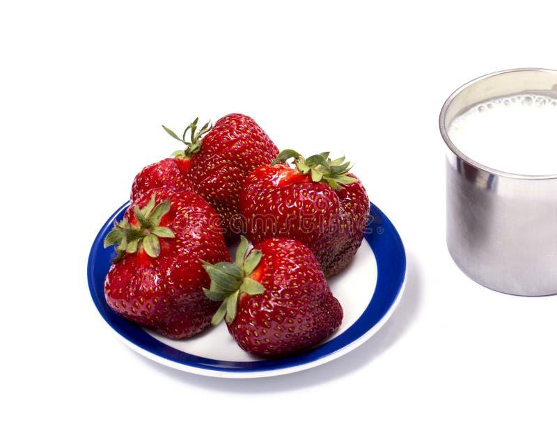 Клубника на поддоннике и стальной кружке молока стоковое изображение rf