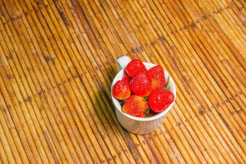 Клубники в чашке, предпосылке ротанга, отборном фокусе на strawberri стоковая фотография
