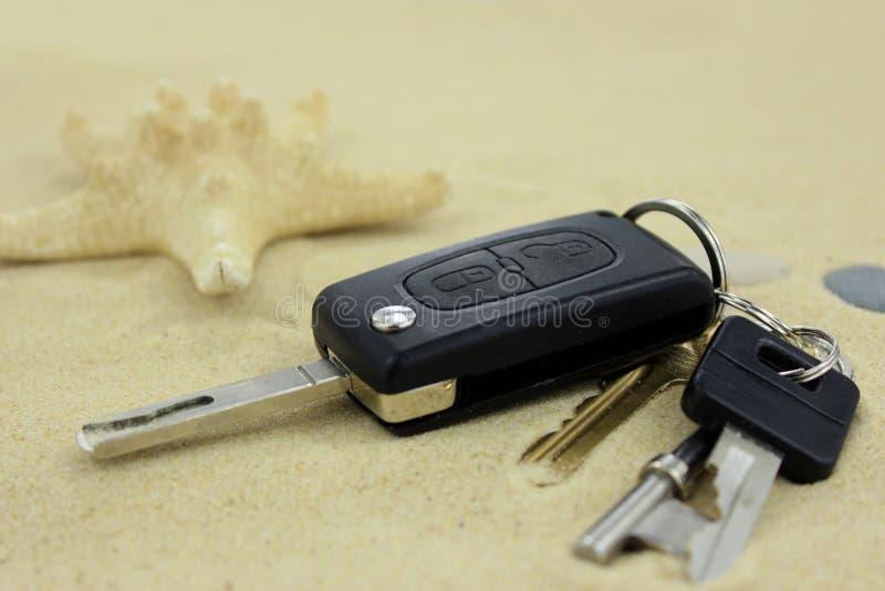 Ключи автомобиля и дома потеряли на песке стоковые фотографии rf