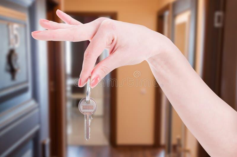 Ключ квартиры в руке женщины стоковые изображения rf