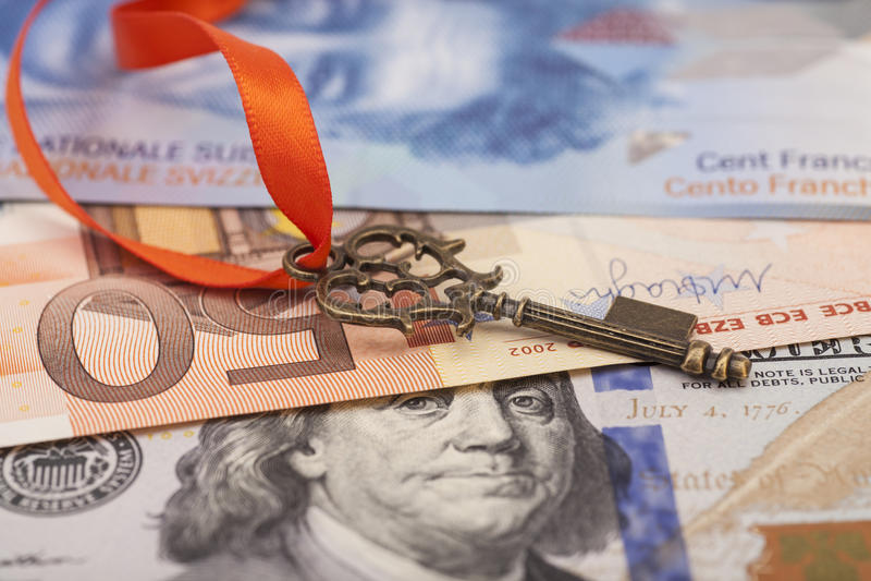 Ключ к успеху с красным смычком на американских долларах, европейским евро, s стоковое фото rf