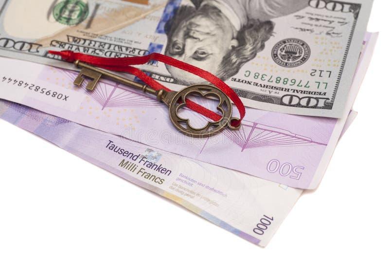 Ключ к успеху с красным смычком на американских долларах, европейским евро, s стоковое изображение