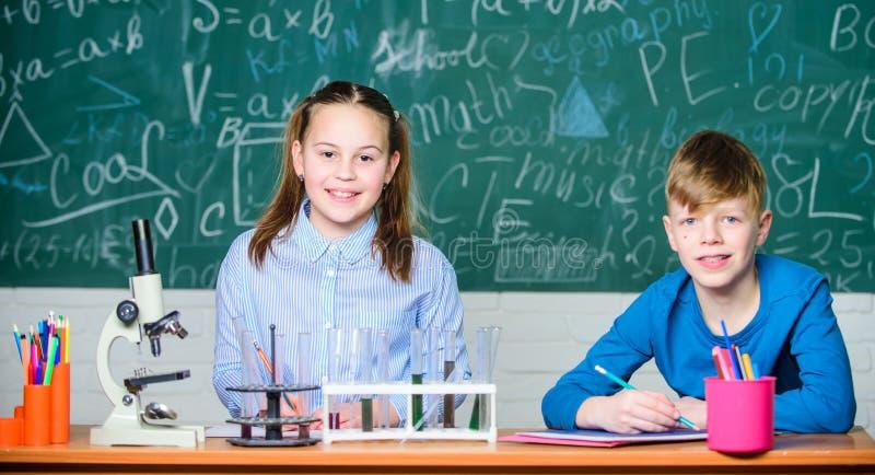 Лаборатория школы Эксперимент по школы проведения студентов девушки и мальчика умный Опишите блокнот химической реакции E стоковое фото rf