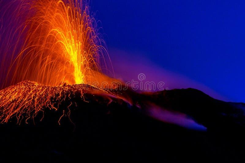 Лава действующего вулкана распыляя в ночу стоковое фото