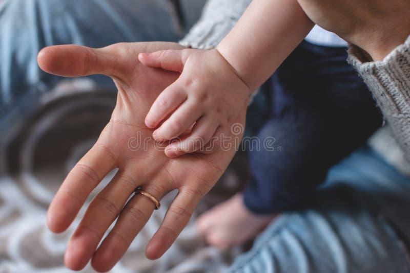 Ладони одно большого человека и небольших детей на других Любовь и предохранение от отца Последовательность поколений стоковое фото rf