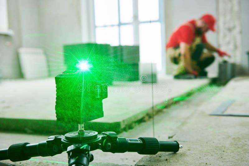 Лазер выравнивая на здании стены построитель каменщика работая с бетонными плитами ceramsite стоковое фото rf