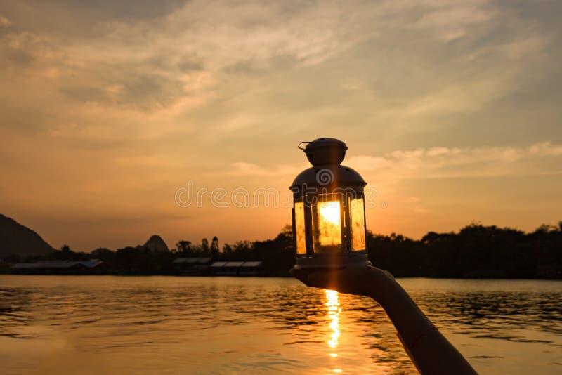 Лампа в наличии в солнечном луче над заходом солнца Концепция силы и идеи стоковое фото