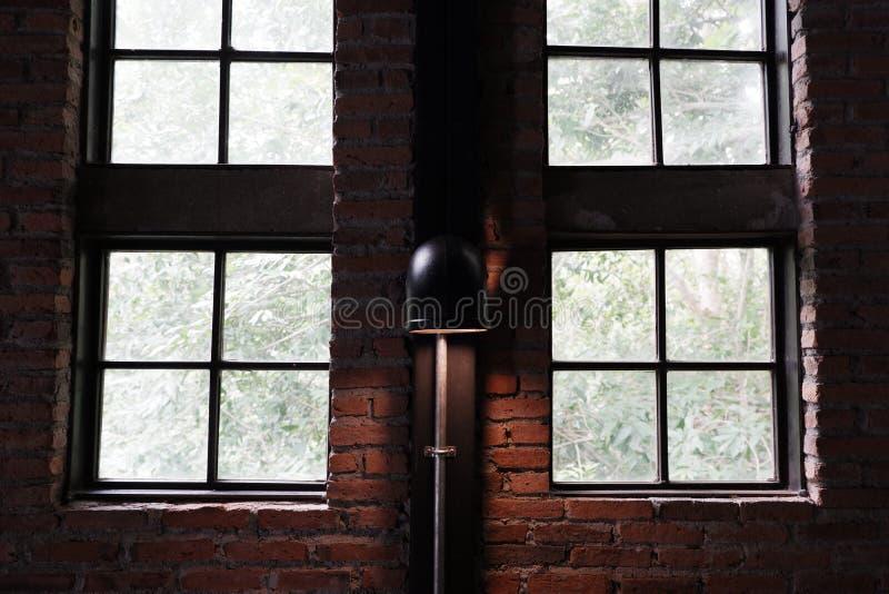 Лампа на кирпичной стене и близко окнах Стиль просторной квартиры стоковые изображения