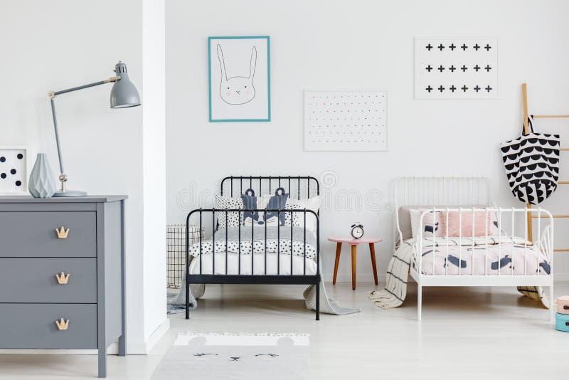 Лампа на сером шкафе в ярком интерьере спальни детей с bl стоковые фотографии rf