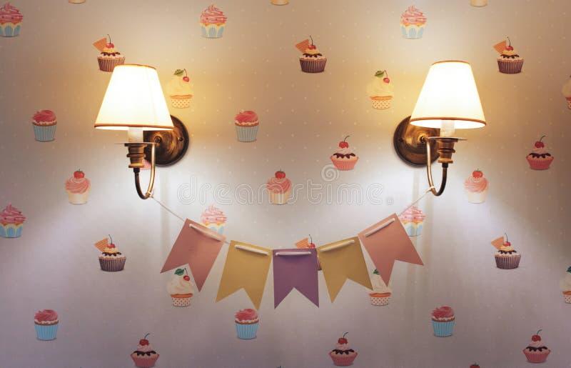 Лампа стены в комнате ` s детей Люстра в комнате ` s детей Конец-вверх Флаги между лампой Обои торта стоковая фотография