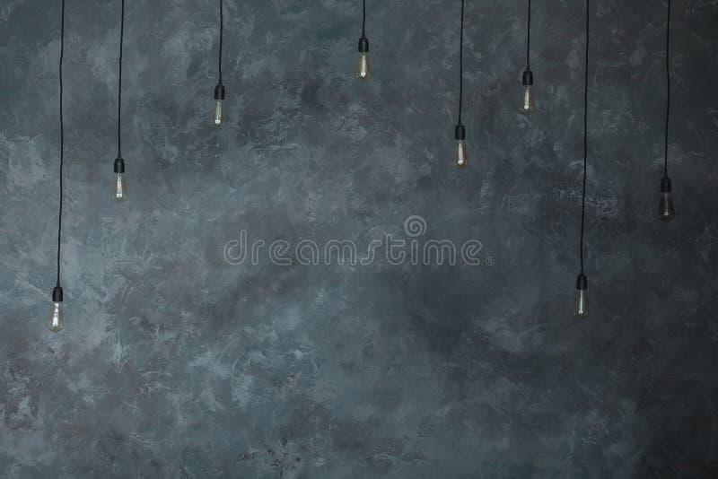 Лампы электрических лампочек на серой стене предпосылки гипсолита Текстура просторной квартиры горизонтальная Винтажная стена в и стоковые изображения