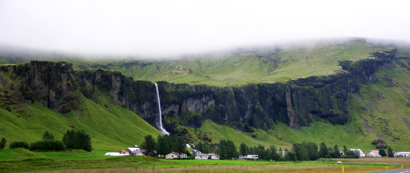 Ландшафт впечатляющих скал с водопадами и ферм в южной Исландии в пасмурном дне стоковое фото