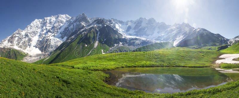 Ландшафт горы Svaneti на день яркого лета солнечный Озеро гор, холмы покрыло зеленую траву на снежных скалистых горах стоковое фото