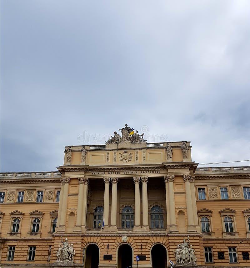 Ландшафт Дом, здание сделанное кирпичей с много статуями Столбцы много окон Небо в облаках стоковое изображение