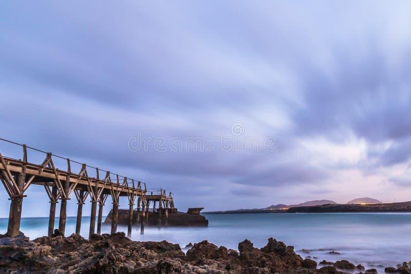 Ландшафт захода солнца с мостом на пляже, облачным небом whit в Канарских островах Лансароте CR2 стоковые изображения
