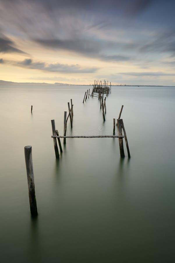 Ландшафт захода солнца artisanal рыбацких лодок в старой деревянной пристани Carrasqueira туристское назначение для посетителей к стоковое изображение