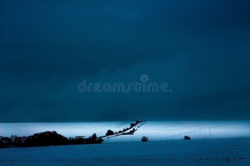 Ландшафт зимы, предпосылка для творческих способностей Дорога в середине поля в зиме, темного бурного sky_ стоковое изображение