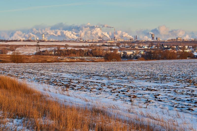 Ландшафт зимы сельский с полем на переднем плане, деревне, погосте на среднем плане и химическом заводе стоковые фотографии rf
