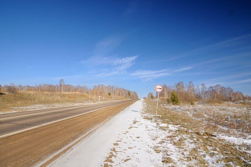 Ландшафт зимы с дорогой асфальта, обнаженными деревьями, первым снегом и никаким настигая дорожным знаком под темно-синим небом стоковые изображения