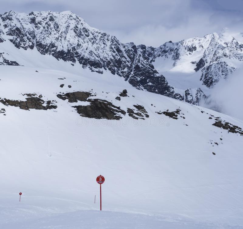 Ландшафт зимы с пустым красным знаком piste, снегом покрыл наклоны горы, день весны солнечный на лыжном курорте Stubai стоковое изображение rf