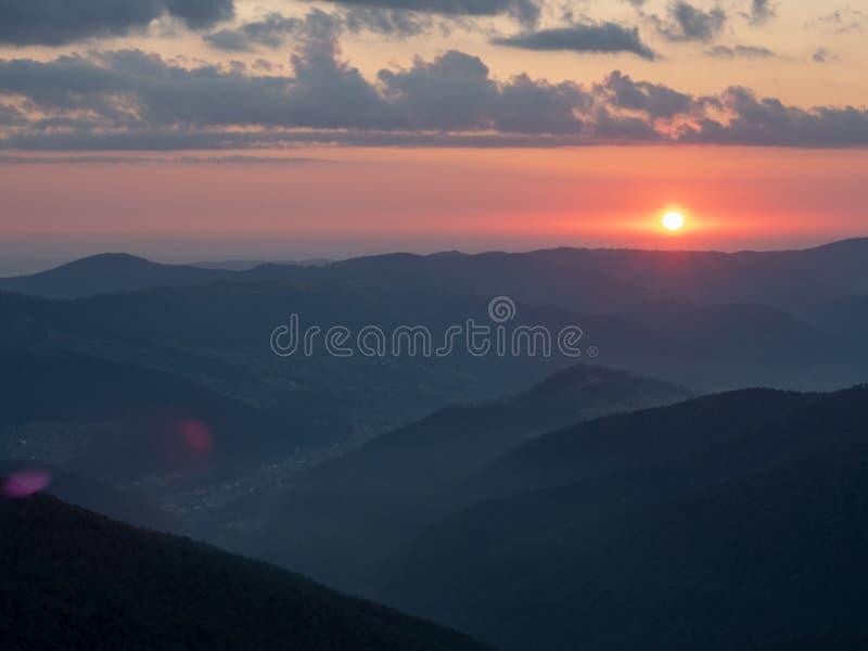 Ландшафт красного захода солнца в горах Горизонт солнца освещающий с красным светом Облака пропуская в небе над темнотой стоковые изображения