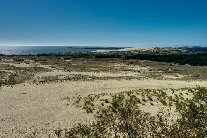 Ландшафт лета с белыми песчанными дюнами, кустами и небом Вертел Curonian, Балтийское море Место всемирного наследия Unesco стоковое фото rf