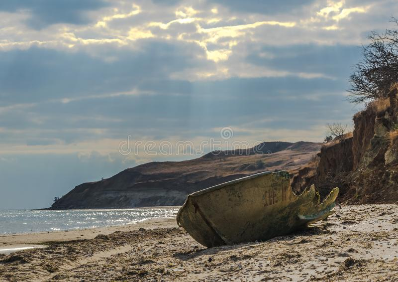 Ландшафт моря дня с загубленной рыбацкой лодкой на переднем плане a стоковые изображения