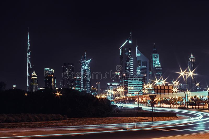 Ландшафт ночи с взглядами небоскребов и Burj Khalifa от стороны дороги стоковое изображение