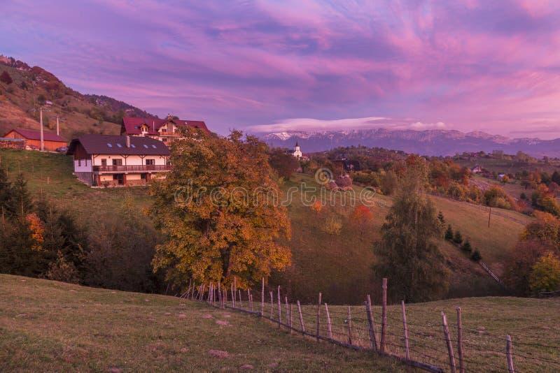 Ландшафт осени высокогорный, высокогорная деревня с эффектными садами и высокие снежные горы в предпосылке около отрубей стоковое фото