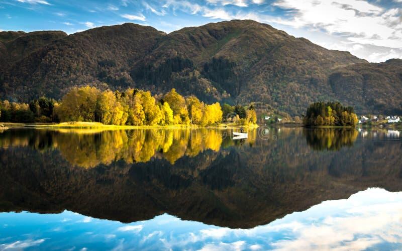 Ландшафт осени с уединенным рыболовом на белой шлюпке, красочных деревьях и горе отраженных в озере стоковые изображения rf