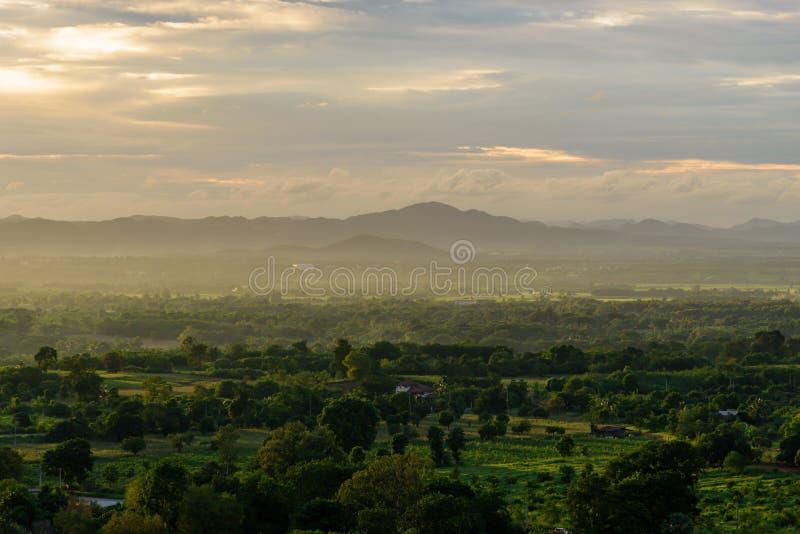 Ландшафт пасмурного, горы и леса с заходом солнца в даже стоковые фото