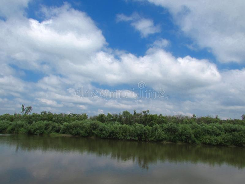 Ландшафт поверхности зеркала ровной спокойного реки с банками, перерастанными кустами и деревьями стоковые фотографии rf