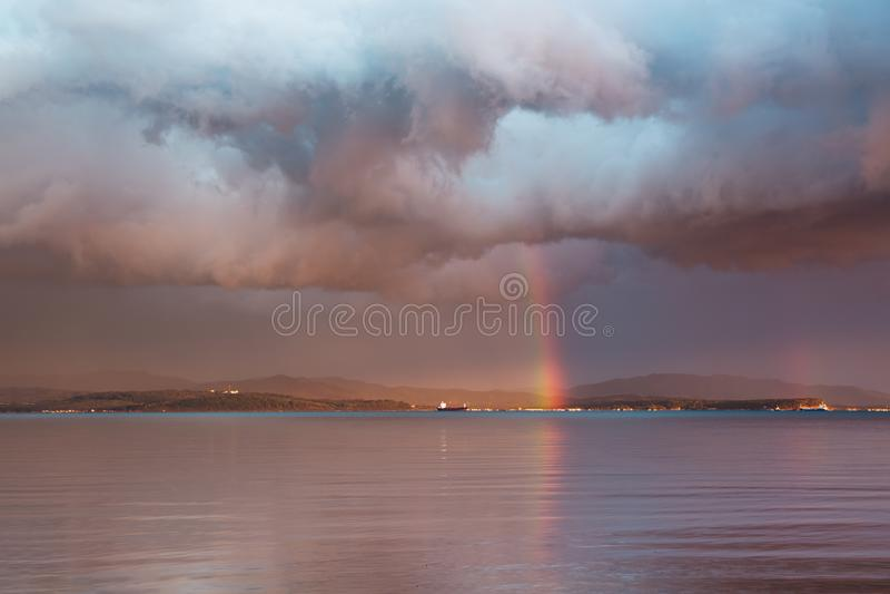 Ландшафт с драматическим небом, ненастными облаками и радугой стоковые фото