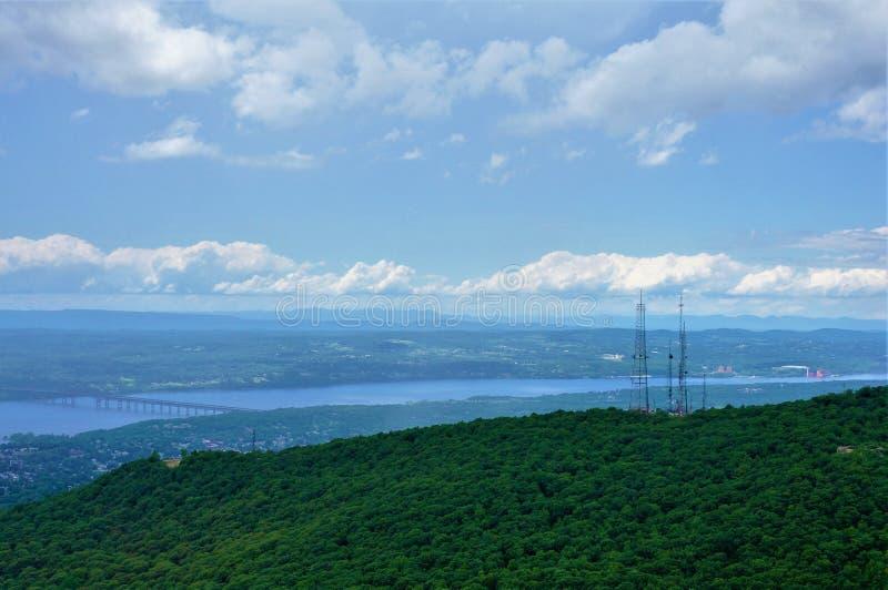 Ландшафт с зелеными холмами с рекой водяной поверхности возможно и мостом на заднем плане Башня мобильного телефона в сторону стоковые изображения rf