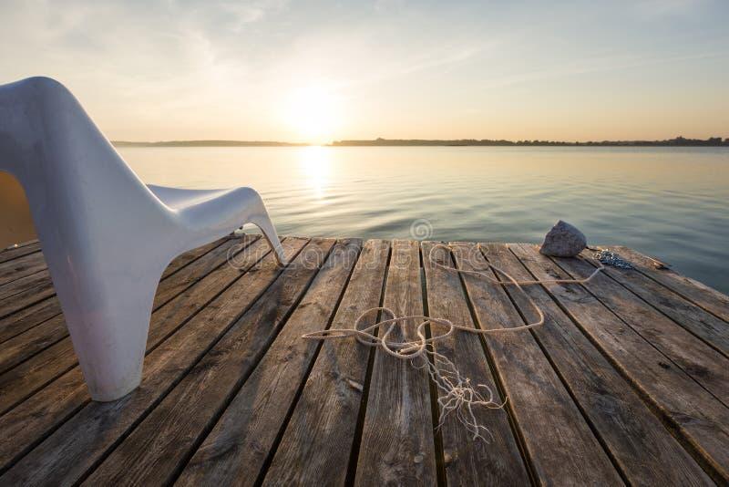 Ландшафт с пустым стулом в деревянном footbridge на озере Powidzkie в Польше стоковые фото