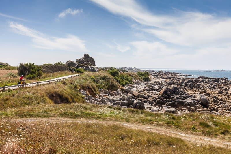 Ландшафт с упакованным велосипедистом на дороге около seashore в Бретани стоковое изображение