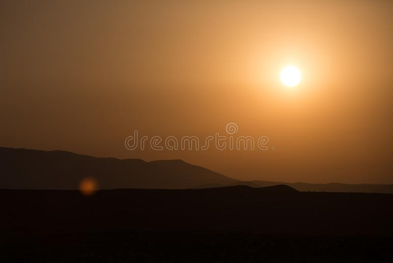 Ландшафт утра с горами и оранжевым небом на восходе солнца с отражать солнца Выравнивать заход солнца на горизонте холмов стоковые изображения