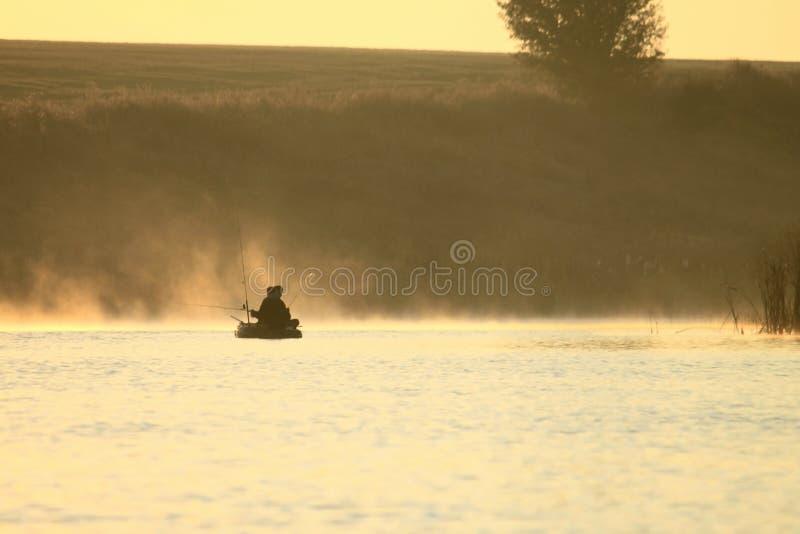 Ландшафт утра с туманом на озере с 2 рыболовами в шлюпке с рыболовными удочками для удить стоковые фотографии rf