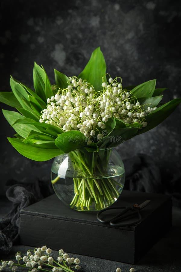 Ландыш цветет в стеклянной вазе, черной предпосылке, стоковые фотографии rf