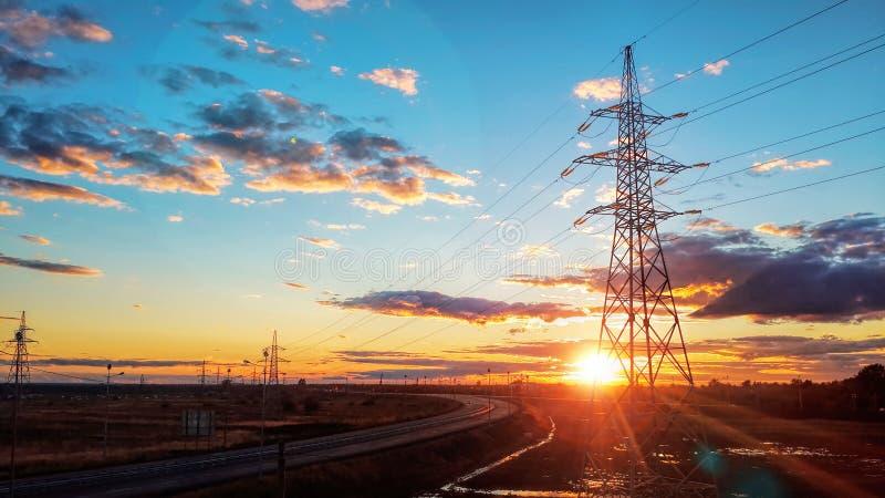 Ландшафт: Высоковольтная электрическая башня на предпосылке захода солнца, дороге, голубом небе и облаках стоковая фотография